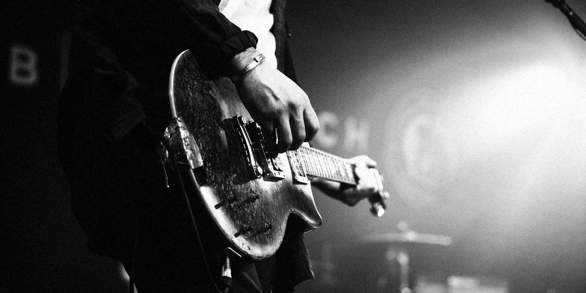 Black and white photo of close up guitarist playing a gig in Cardiff